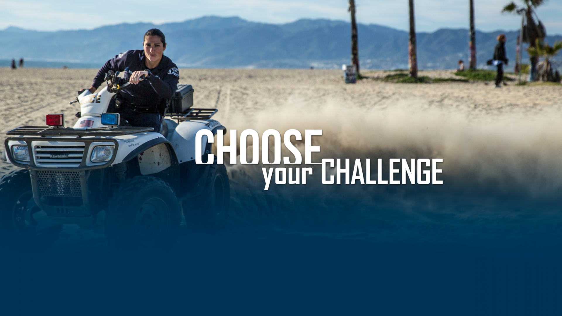 Female Officer riding ATV through sandy beach